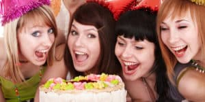 Group of smiling young women crowded around a cake at an 18th birthday party